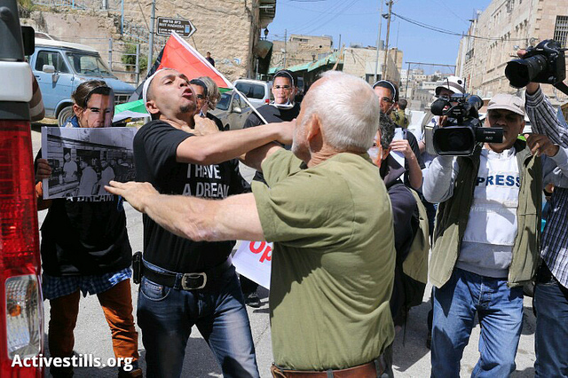 Izraelský osadník uhodil demonstranta při protestu v Hebronu proti plánované návštěvě prezidenta USA Baracka Obamy na Západním břehu Jordánu. Hebron, 20. března. (Foto activestills.org)