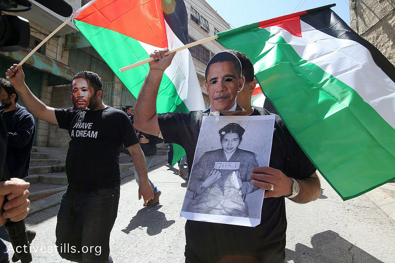Protestující s maskami Martina Luthera Kinga a Baracka Obamy při demonstraci proti plánované návštěvě amerického prezidenta na Západním břehu Jordánu. Hebron, 20. března. (Foto: activestills.org)