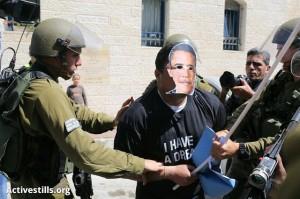 Demonstrant s maskou Baracka Obamy zadržený izraelskou armádou při protestu proti plánované návštěvě amerického prezidenta na Západním břehu Jordánu. Hebron, 20. března. (Foto: activestills.org)