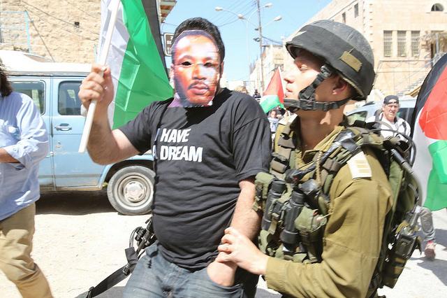 Demonstrant s maskou Martina Luthera Kinga zadržený izraelskou armádou při protestu proti plánované návštěvě prezidenta USA Baracka Obamy na Západním břehu Jordánu. Hebron, 20. března. (Foto: activestills.org)