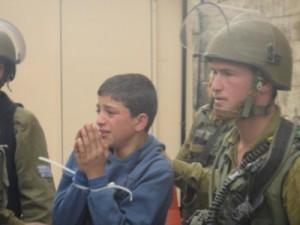 Jedno ze zatčených dětí odváděné do armádního džípu