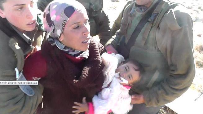 Izraelské okupační jednotky zatýkají nenásilně protestující Reemu a její 18měsíční dcerku Quamar v Umm Al Arayes, kopce jižního Hebronu (foto: Ta'ayyush)